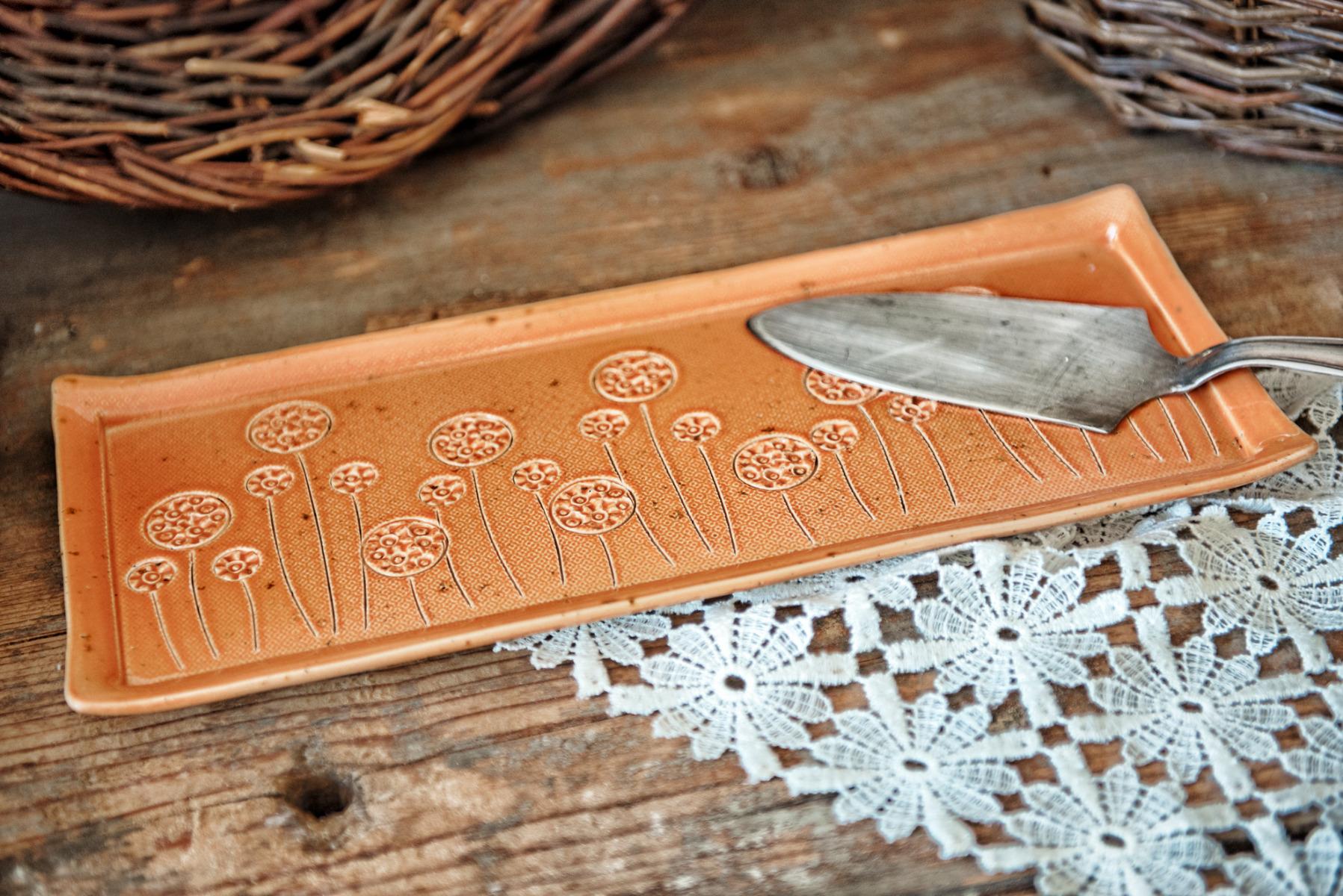 Ein Kuchentablett mit Blumen, die liebevoll mit Hand in den Ton geritzt werden.